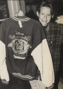 Jonathan Taylor Thomas holding the Disney Television Broadcast 40th anniversary jaket, while visiting the Disney souvenier store in Cleveland, Ohio.