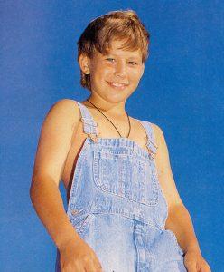 Jonathan Taylor Thomas wearing overalls.